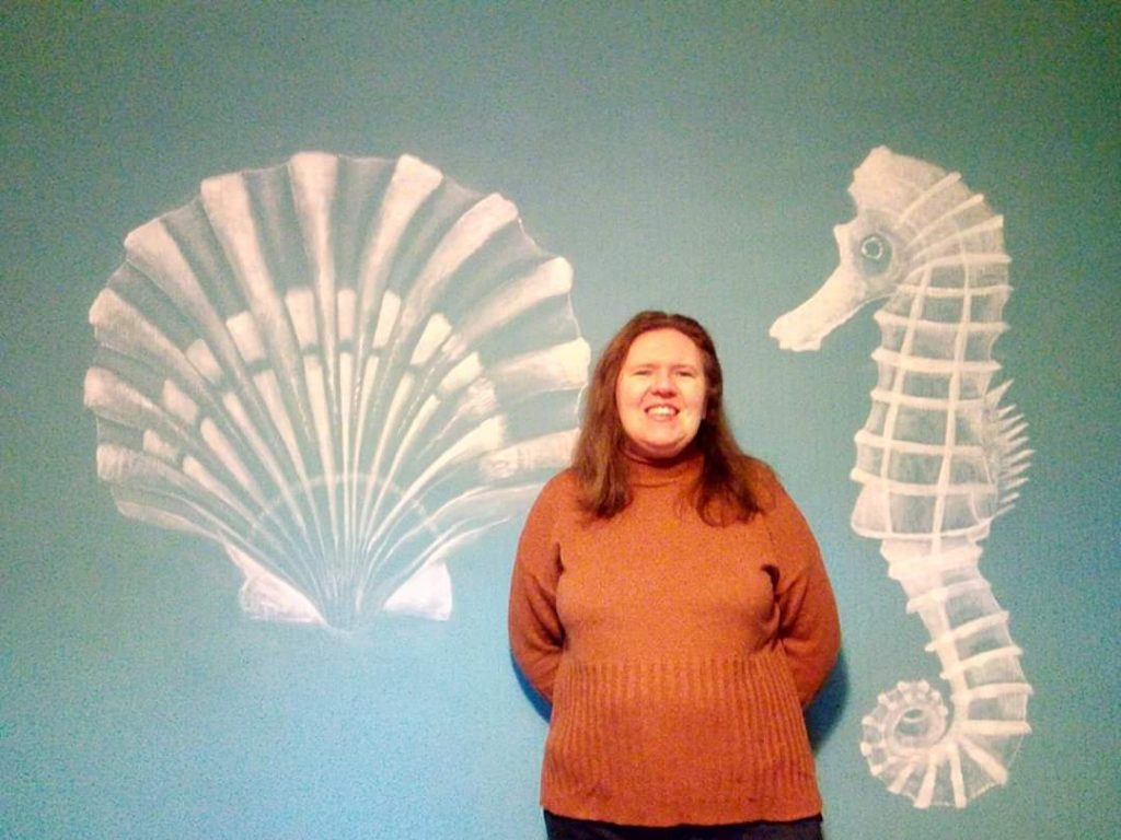 Helen in front of mural creation of seahorse and scallop shell